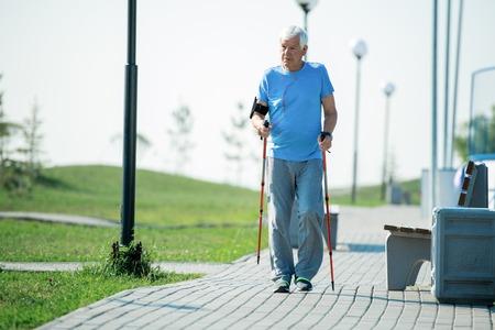 Moderner älterer Mann, der mit Polen geht