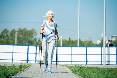 Glückliche ältere Frau Nordic Walking Standard-Bild