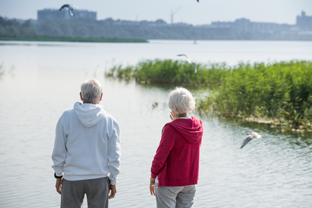 Active Senior Couple Watching Seagulls on Lake Stock Photo