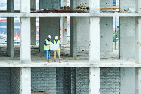 Two Builders Holding Construction Plans 写真素材
