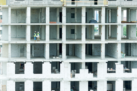 Construction workers on building site of apartment house