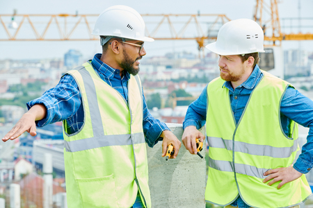 Mixed race construction engineer talking to coworker