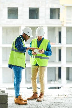 Compañeros de trabajo ocupados discutiendo el plan de trabajo de construcción