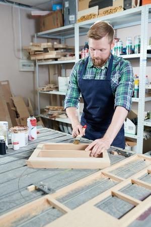 Carpenter varnishing wood