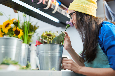 Young Woman Smelling Flowers in Shop