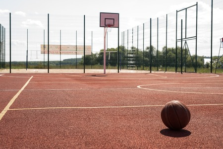 Wide angle shot of empty outdoor basketball court lit by sunlight with hoop and ball on floor in foreground, copy space