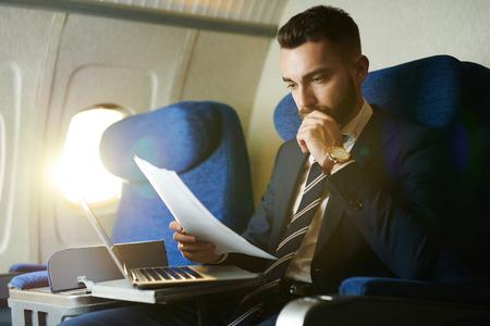 Moderne zakenman die in vliegtuig werkt Stockfoto