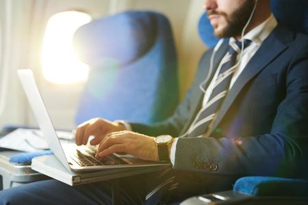 Geschäftsmann, der Laptop in Flugzeug-Nahaufnahme verwendet Standard-Bild