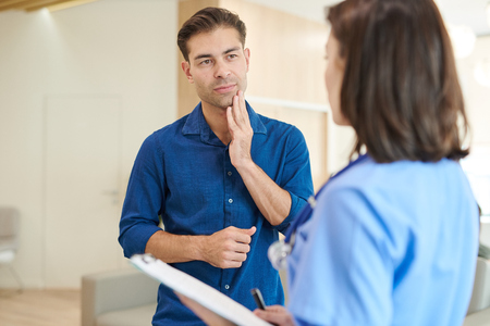 Man Explaining Symptoms to Nurse Stock Photo - 108969275