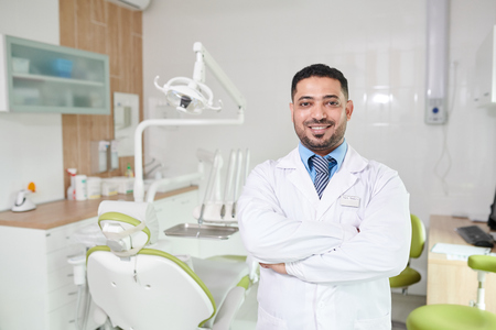 Middle-Eastern Dentist Posing at Workplace