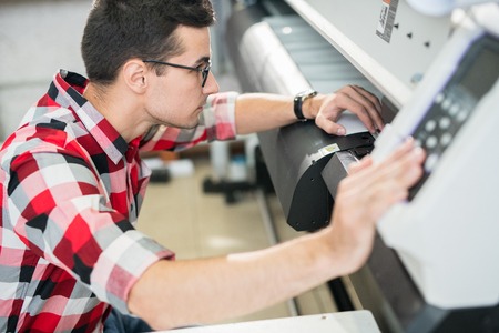 Ingeniero examinando la impresora de gran formato Foto de archivo