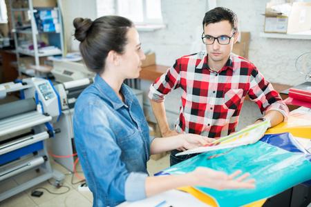 Pensive printing specialists analyzing paper Reklamní fotografie