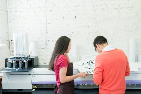 Printing specialists examining banner in office