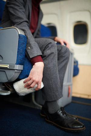Portrait of unrecognizable man hiding bag of drugs under seat in plane dropping illegal substances, copy space