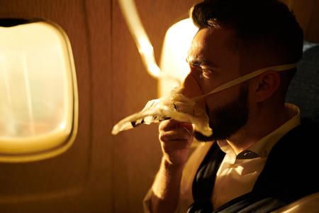 Mann, der Sauerstoff im Flugzeug atmet Standard-Bild