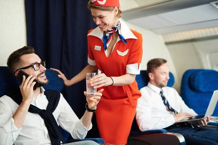 Auxiliar de vuelo que sirve bebidas Foto de archivo