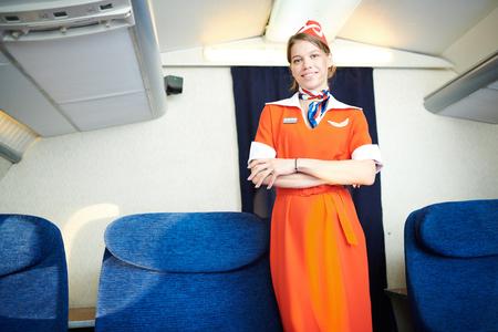 Smiling Flight Attendant Posing in Plane Stock Photo
