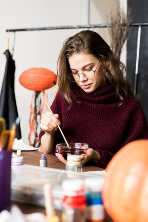 Creative artist mixing paint in bowl