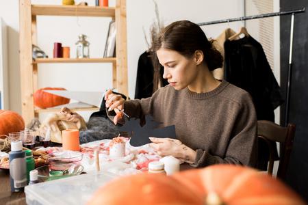 Serious craftswoman making Halloween decoration 스톡 콘텐츠