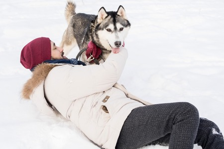 Carefree Man Playing with Dog in Snow