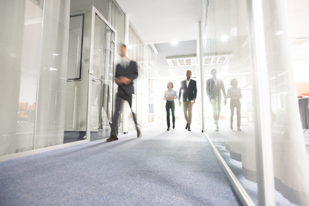 Gente di affari che cammina nel corridoio dell'ufficio Archivio Fotografico