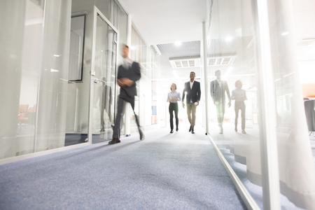 Mensen uit het bedrijfsleven lopen in de kantoorgang Stockfoto