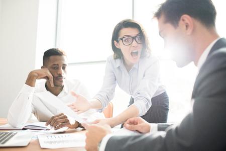 La patronne furieuse criant au subordonné lors d'une réunion Banque d'images