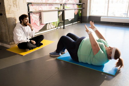 Obese Woman Working Out on Floor Stock Photo