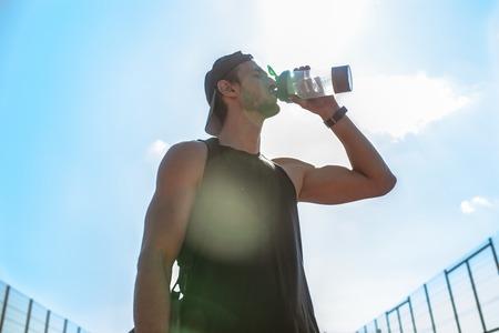 Muscular Sportsman Drinking Water Outdoors Banco de Imagens