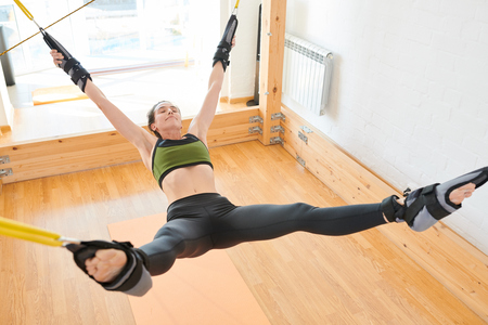 Content young woman strapped to yoga swing