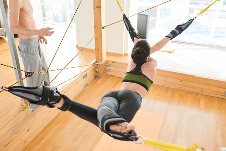 Slim woman practicing yoga on trapeze Stock Photo