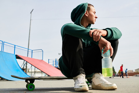 Young Man Sitting on Skate Stock Photo