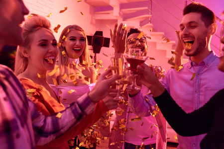 Laughing friends with confetti and champagne on party