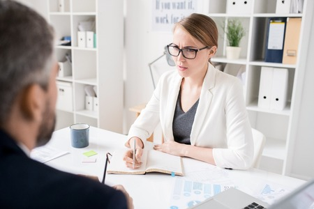 Displeased lady boss talking to colleague