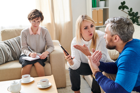 Sad wife fighting with cheating husband at therapy session Stock Photo