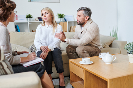 Sad husband apologizing to wife at therapy session Stock Photo