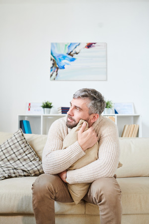 Emotionally instable man embracing cushion in psychiatrists room