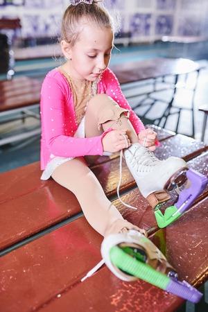 Chica poniéndose zapatos de patinaje