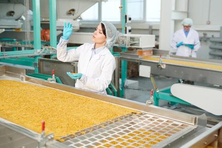 Young Woman at Food Conveyor Foto de archivo