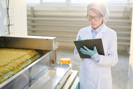 Woman Working at Factory in Sunlight Stock Photo