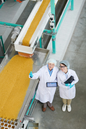Two Workers Overseeing Production at Factory 写真素材