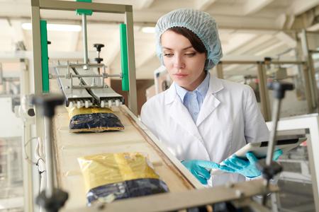 Jonge vrouw die de verpakkingslijn controleert