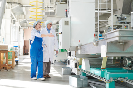 Young Woman Presenting Factory Equipment Standard-Bild - 112556610