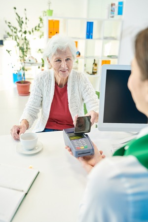 Senior bank client drinking coffee while paying with smartphone Stockfoto