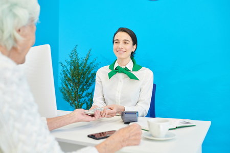 Cheerful manager getting money from customer for deposit Stockfoto