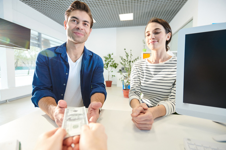 Satisfied couple taking money in bank office