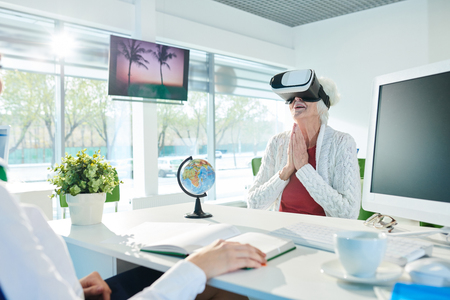 Cheerful senior lady watching 3D video of hotel presentation