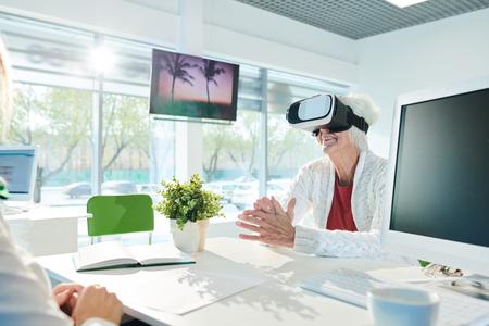 Happy senior lady in VR simulator enjoying virtual tour