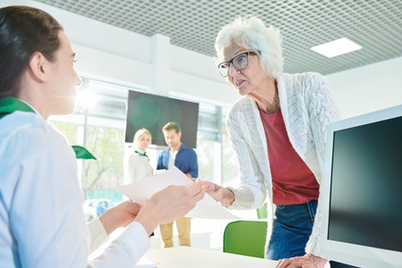 Outraged senior lady speaking loudly in travel agency office Stock Photo