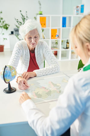 Elderly lady asking travel agent about tour